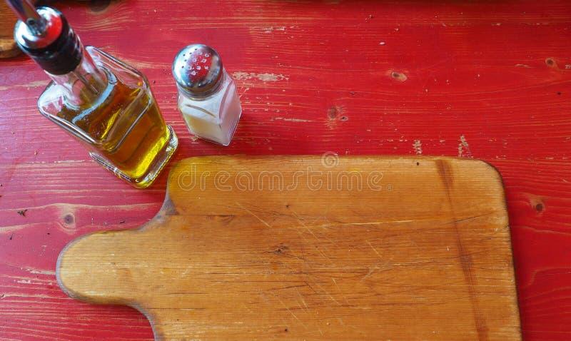 planche à découper en bois avec l'huile et le sel d'olive image libre de droits
