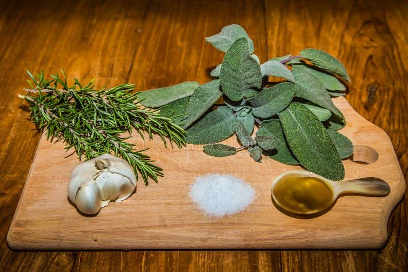 Planche à découper en bois avec les herbes, le pétrole, le sel et l'ail image libre de droits