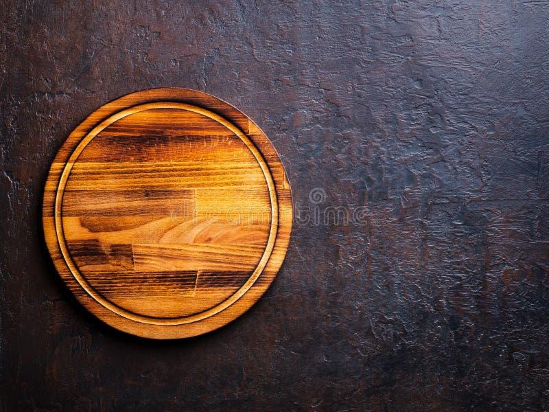 Planche à découper en bois brune foncée de rond vide sur le Ba en pierre brun foncé image libre de droits