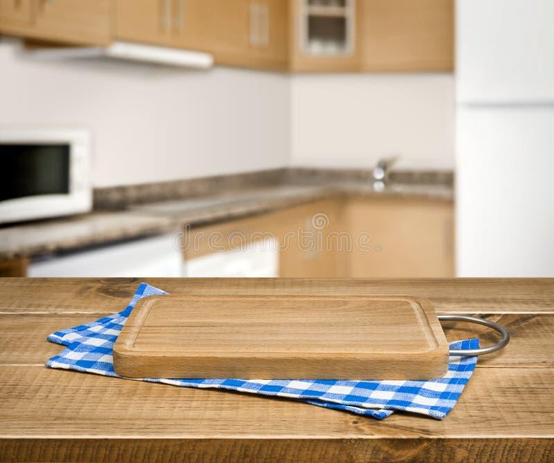 Planche à découper en bois, serviette à carreaux bleue au-dessus de fond brouillé de cuisine photos stock