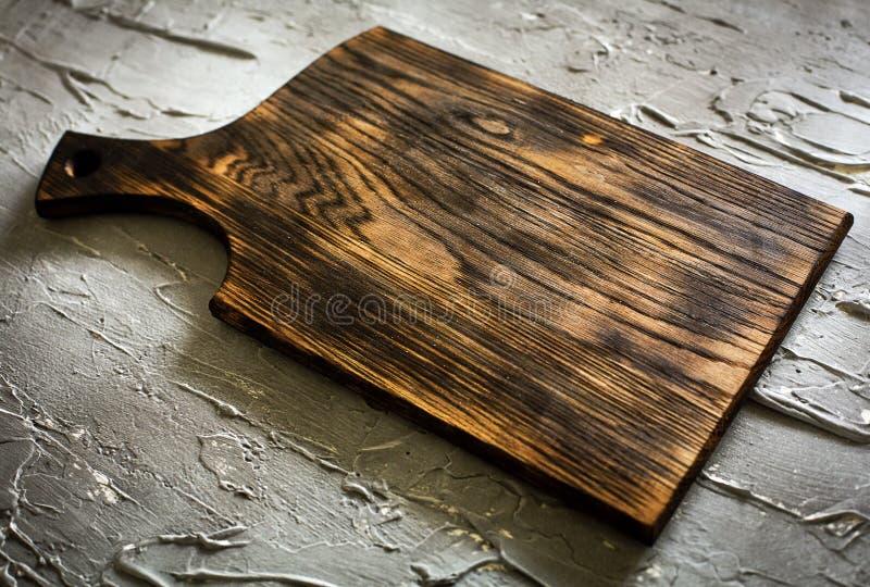 Planche à découper en bois sur un fond concret photos libres de droits
