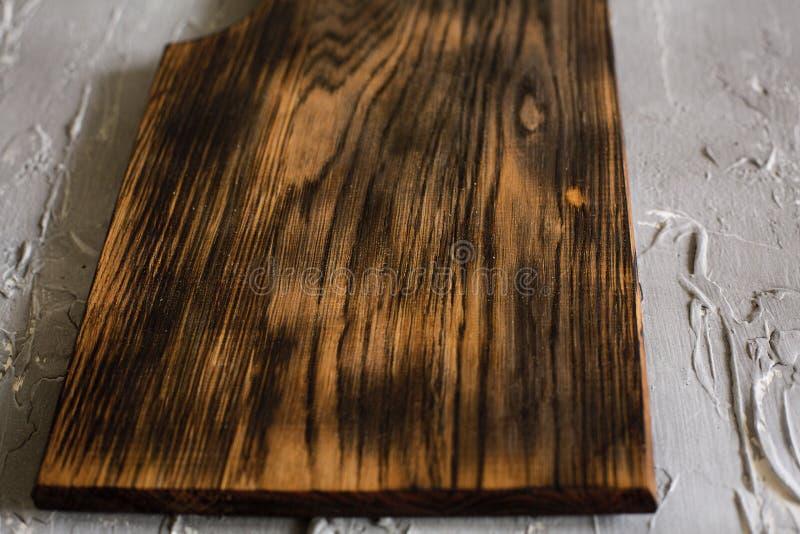 Planche à découper en bois sur un fond concret images libres de droits