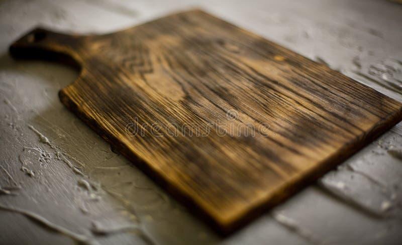 Planche à découper en bois sur un fond concret image stock