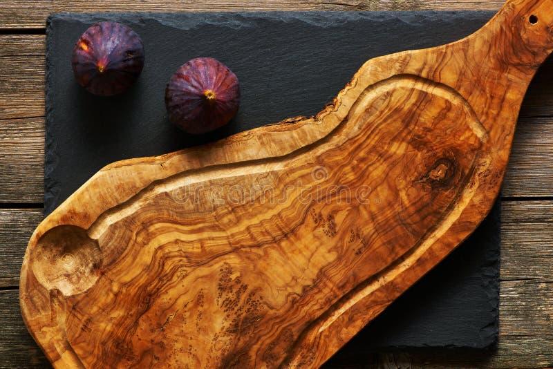 Planche à découper et figues en bois olives image libre de droits