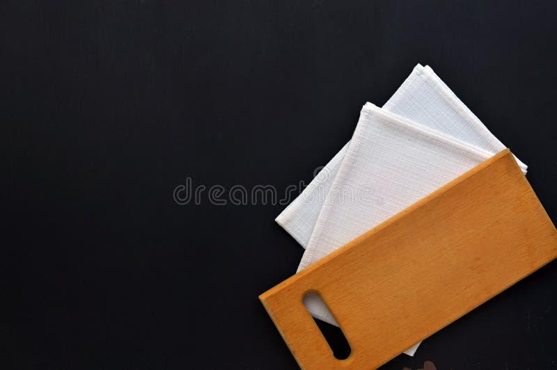 Planche à découper et serviette sur un fond en bois foncé Vue supérieure Le concept de la cuisson Fond de cuisine photographie stock