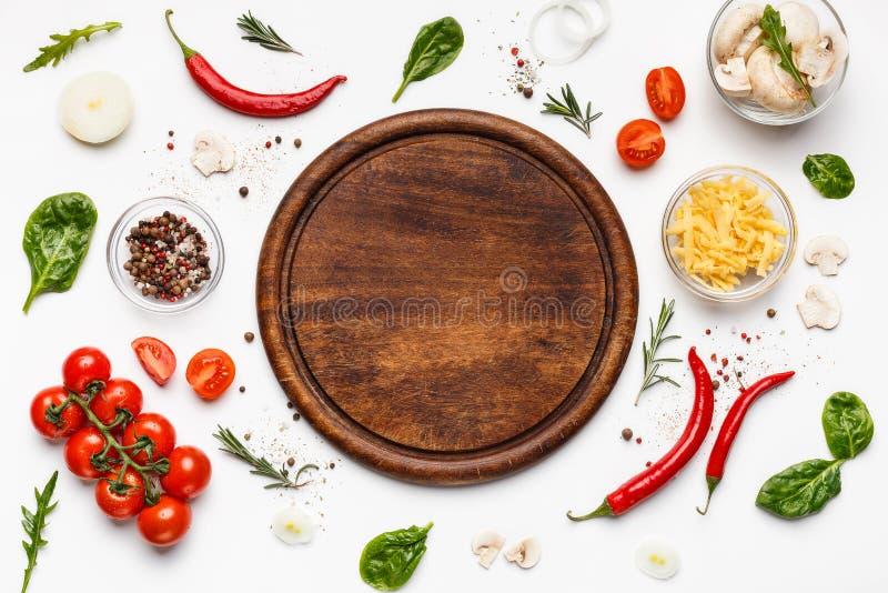 Planche à découper ronde avec des ingridients de pizza autour image stock