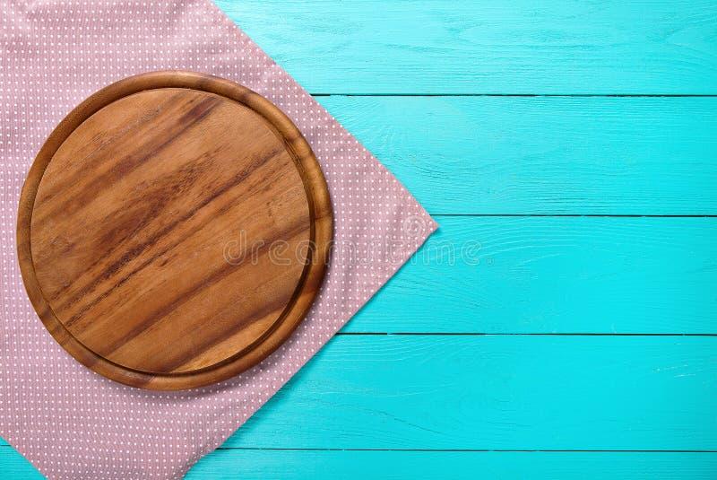 Planche à découper ronde de pizza de Brown sur la nappe de points de polka Fond en bois bleu dans le restaurant Copiez l'espace,  photo libre de droits