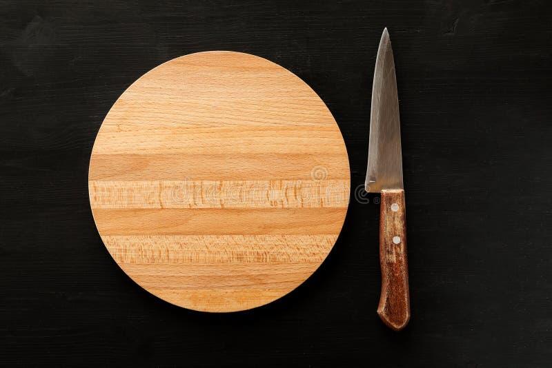 Planche à découper ronde en bois vide avec le couteau sur un fond noir, vue supérieure photos libres de droits