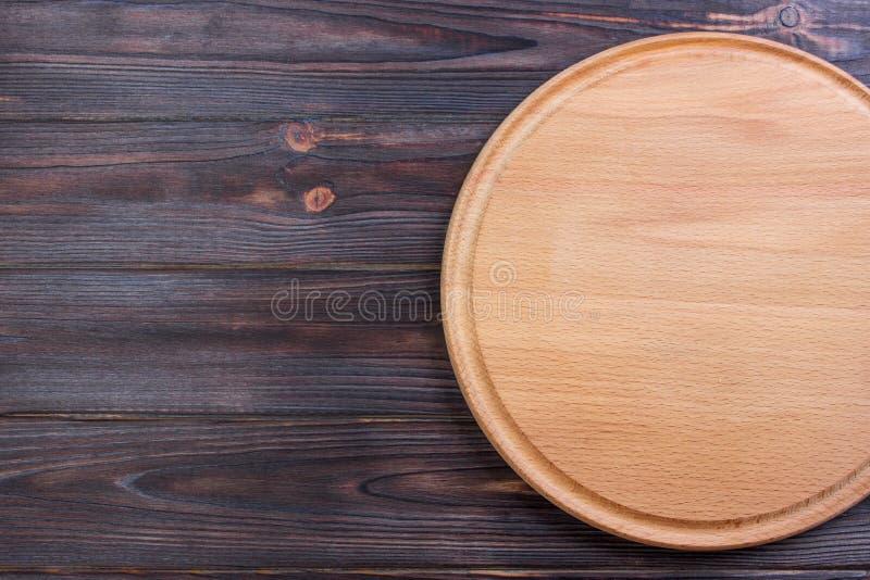 Planche à découper ronde sur le vieux fond en bois de texture image libre de droits