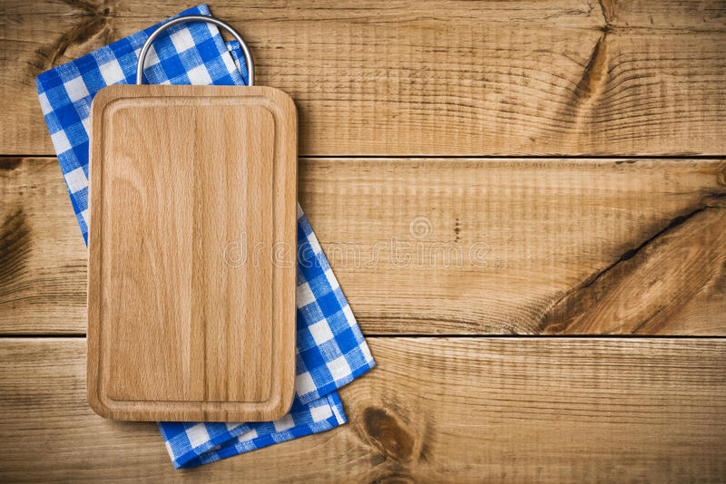 Planche à découper sur la serviette de cuisine bleue avec le copyspace de côté droit images stock