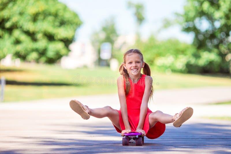 Planche à roulettes adorable d'équitation d'enfant en parc d'été photos stock