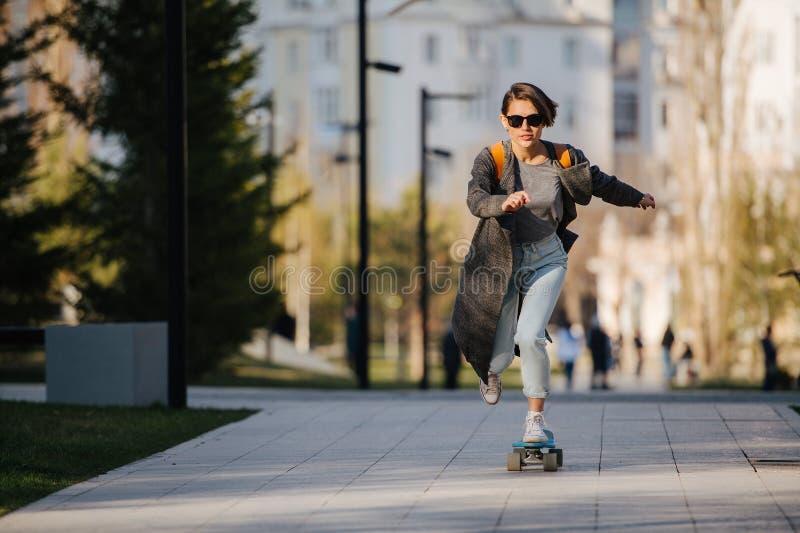 Planche à roulettes attrayante d'équitation de jeune femme en parc photo libre de droits