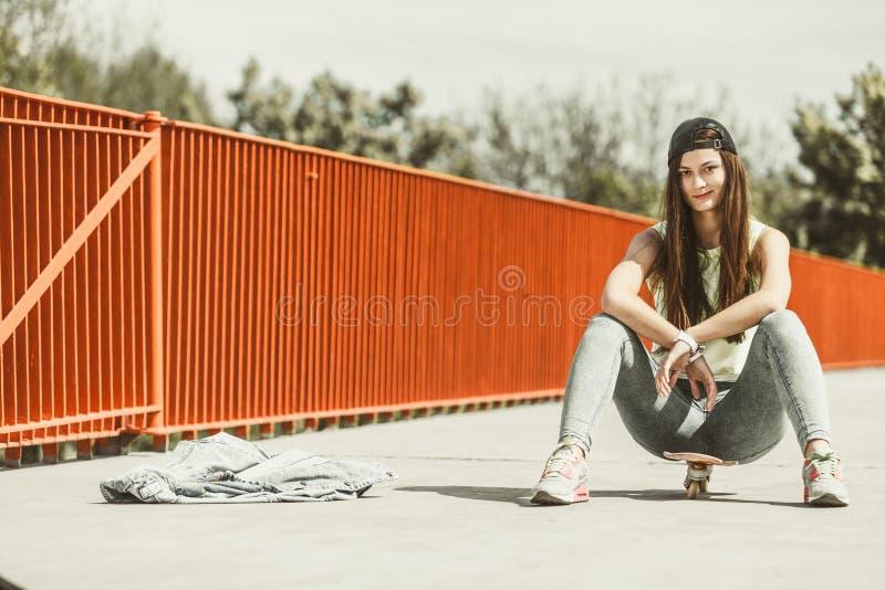 Planche à roulettes d'équitation de patineuse d'adolescente sur la rue image stock