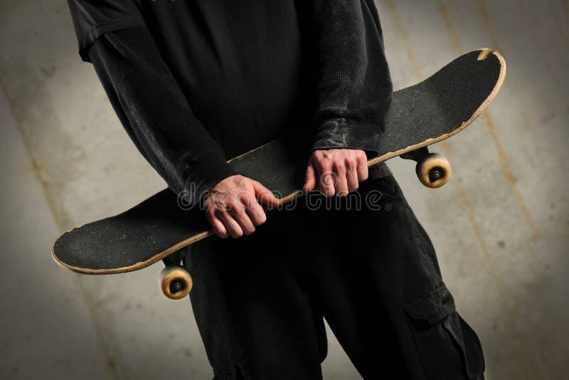 Planche à roulettes de fixation d'homme photographie stock