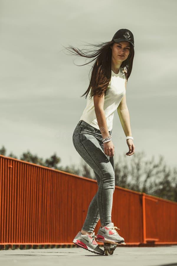 Planche à roulettes de l'adolescence d'équitation de patineuse de fille sur la rue photos libres de droits