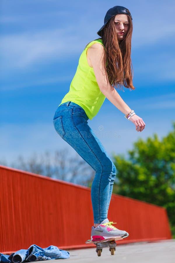 Planche à roulettes de l'adolescence d'équitation de patineuse de fille sur la rue photo libre de droits