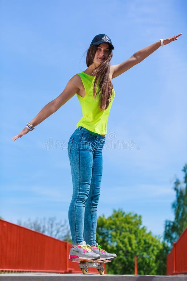 Planche à roulettes de l'adolescence d'équitation de patineuse de fille sur la rue image libre de droits