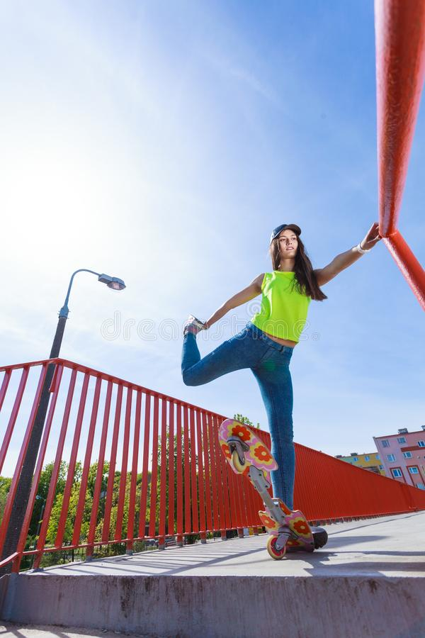 Planche à roulettes de l'adolescence d'équitation de patineuse de fille sur la rue photographie stock