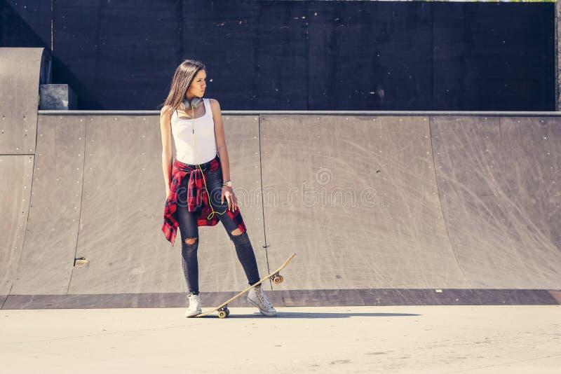 Planche ? roulettes mignonne de participation de fille en parc de patin image libre de droits