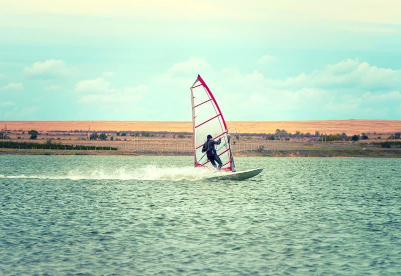 Planche à voile active de loisirs de l'eau de navigation de sport de planche à voile sur le LAK photographie stock libre de droits