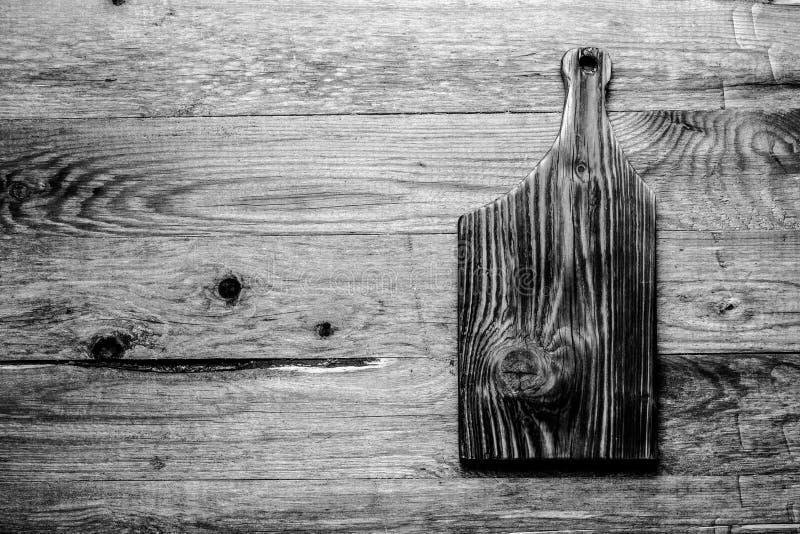Planche ? d?couper br?l?e faite main sur une texture rustique en bois pour le fond Conseil en bois superficiel par les agents app photo stock