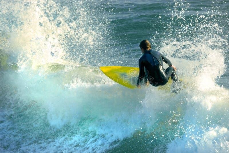 Planche de surfing jaune, les eaux bleues image libre de droits