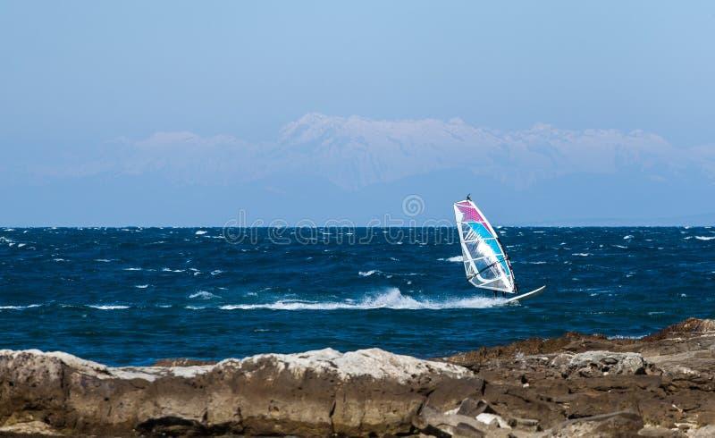 Planche ? voile sur la Mer Adriatique entour?e par des montagnes d'Alpes photos libres de droits