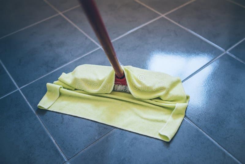 Plancher carrelé de essuyage humide avec du chiffon de nettoyage de plancher image stock