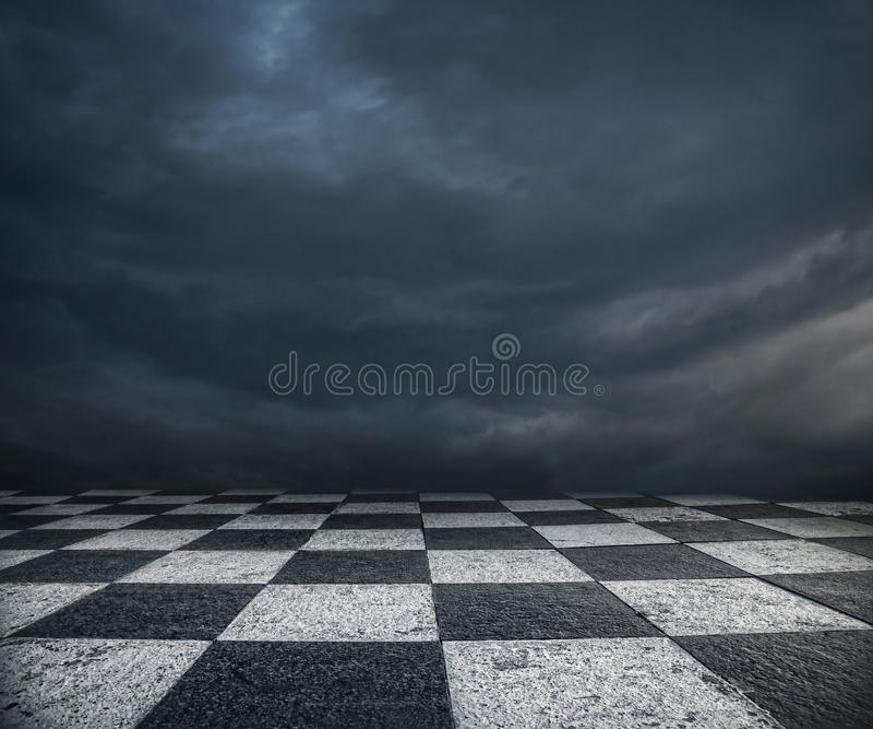 Plancher d'échecs et fond foncé de ciel photo stock