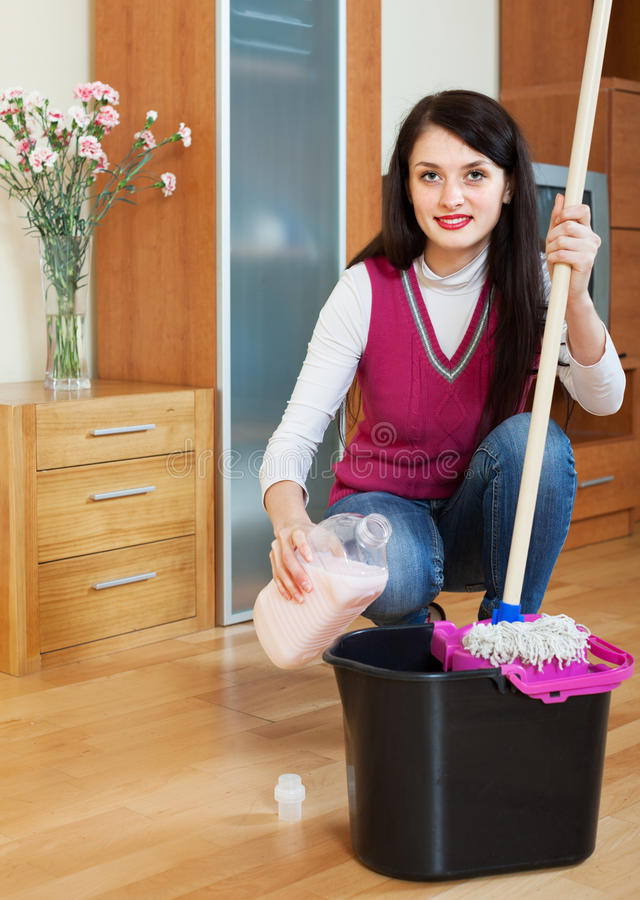 Plancher de lavage de sourire de femme de brune avec le détergent images stock