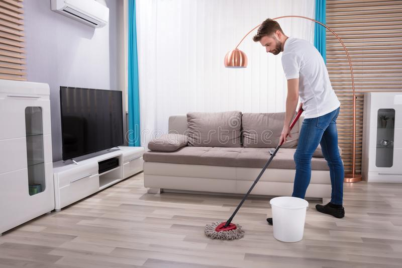 Plancher de nettoyage d'homme avec le balai images libres de droits
