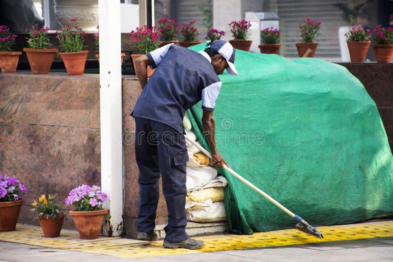 Plancher de nettoyage d'hommes de décapant indien de travailleur au jardin de parc de patio du magasin au matin de ville de Delhi image libre de droits