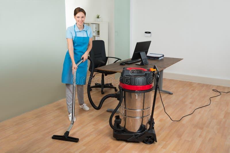 Plancher de nettoyage de travailleur avec l'aspirateur image libre de droits