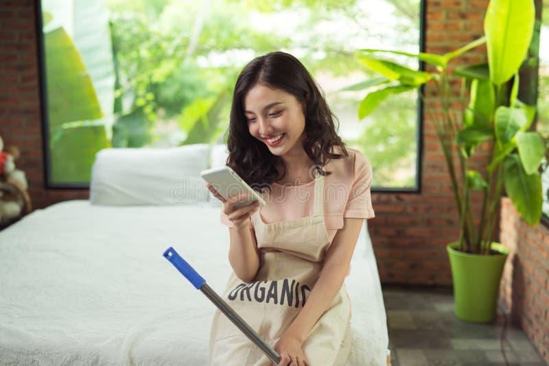 Plancher de nettoyage de femme avec le balai à l'intérieur Détendez après avoir fait le housewo photographie stock libre de droits