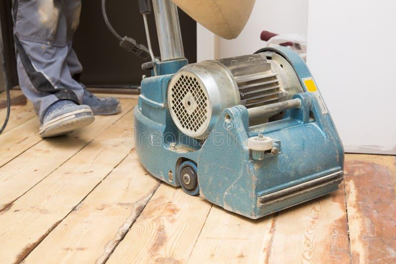 Plancher de planche de restauration avec la machine de meulage photographie stock