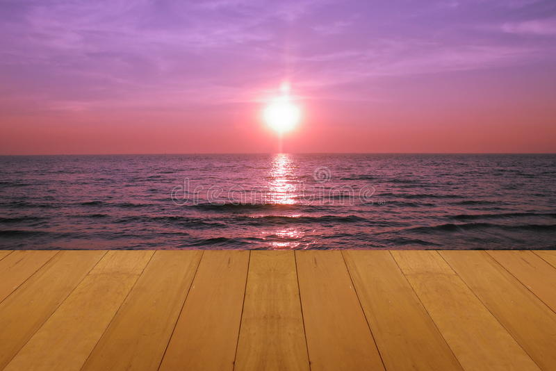Plancher en bois sur la mer avec le coucher du soleil pourpre brûlant la belle mer tropicale naturelle de Skie image stock