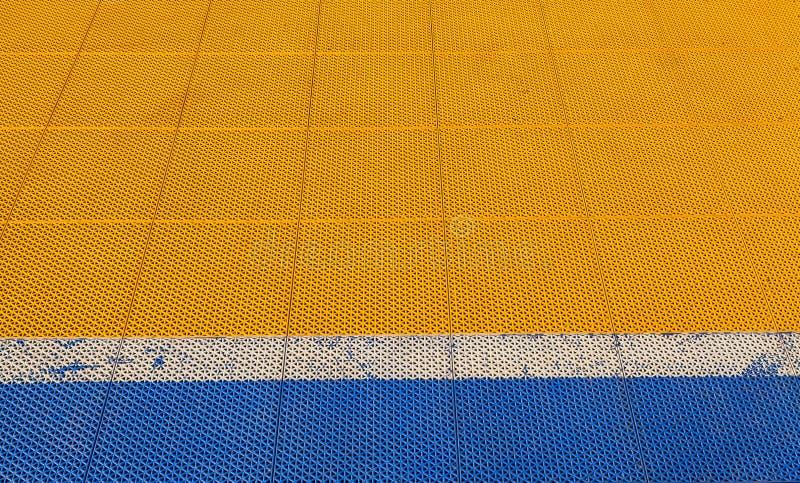 Plancher en caoutchouc bleu et jaune sur le fond de champ de Futsal photographie stock libre de droits