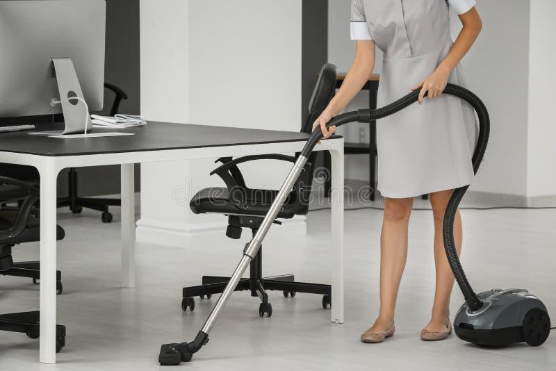 Plancher hoovering de jeune femme dans le bureau utilisant le décapant image libre de droits