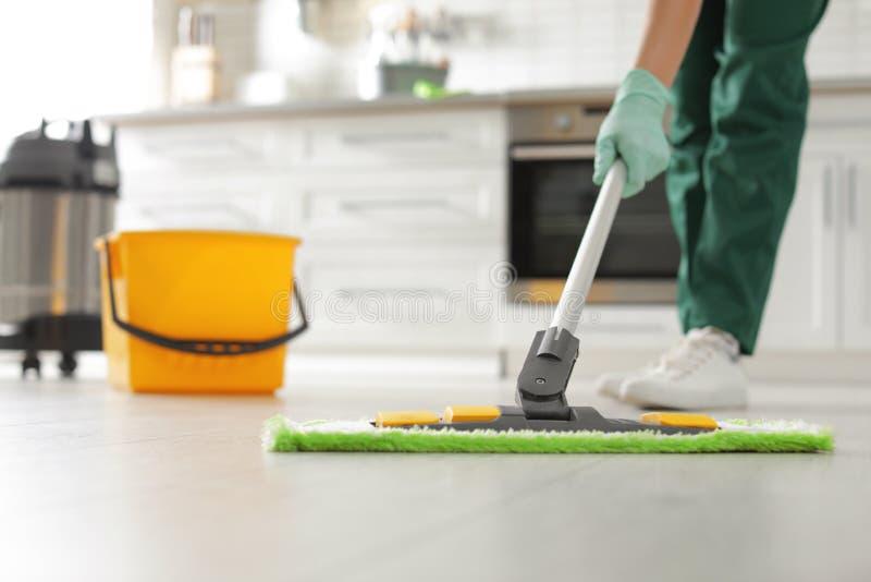 Plancher professionnel de nettoyage de portier avec le balai dans la cuisine photo stock