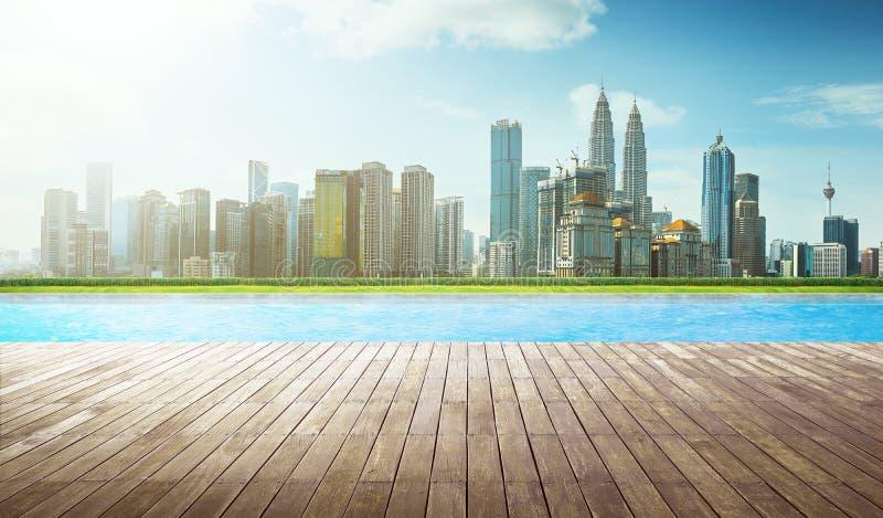 Plancher vide de brun en bois de perspective devant la piscine avec l'horizon de ville photo libre de droits