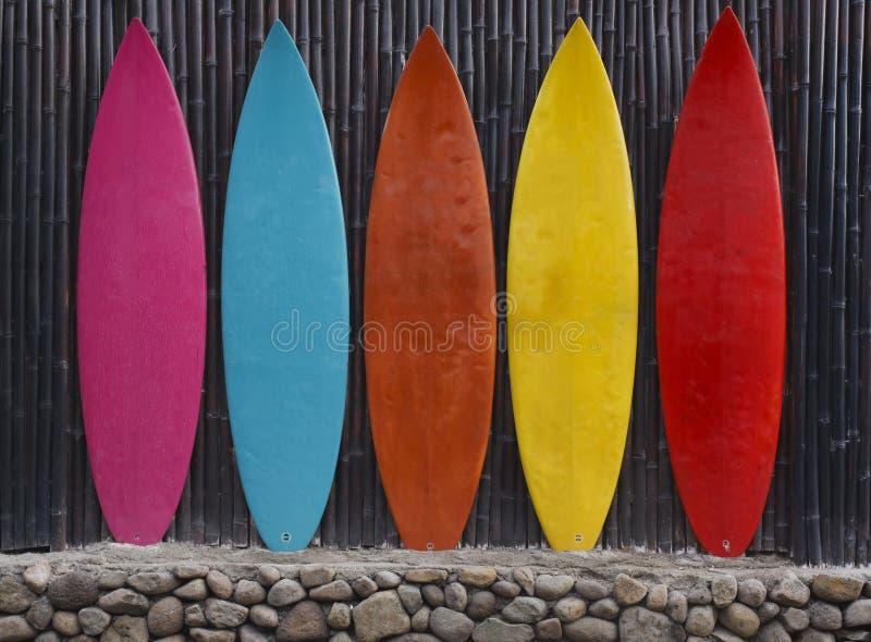 Planches de surf colorées se penchant contre une barrière en bois image libre de droits