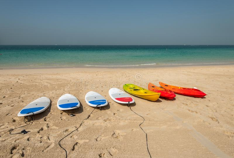 Planches de surf et kayaks sur la plage sablonneuse images stock