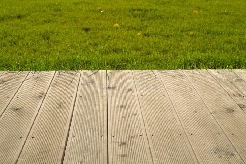 Planches en bois avec l'herbe verte photos stock