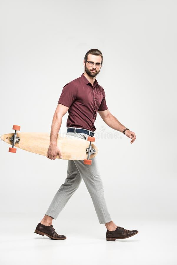 planchiste beau posant avec le longboard, photo stock