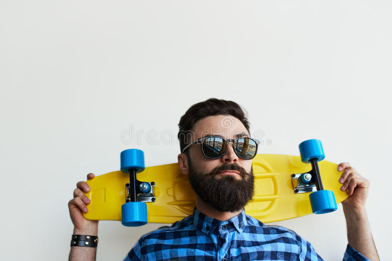 Planchiste beau, tenant une planche à roulettes derrière sa tête photographie stock