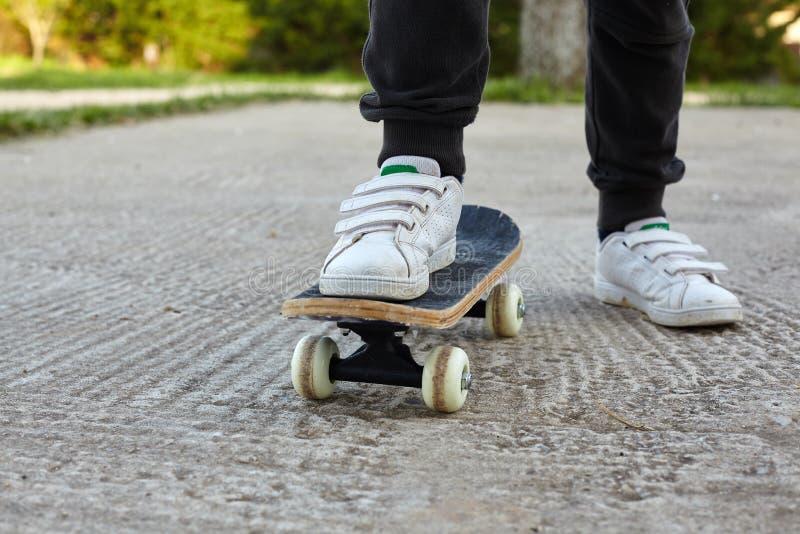 Planchiste d'enfant faisant un tour de planche à roulettes images libres de droits