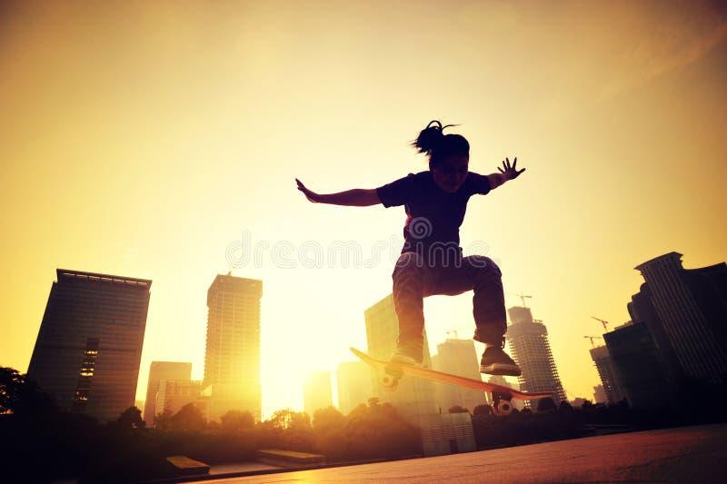 Planchiste de femme faisant de la planche à roulettes à la ville de lever de soleil photographie stock