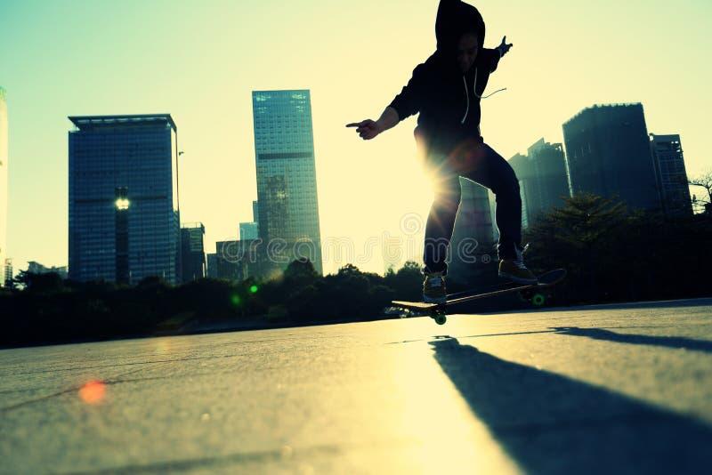 Planchiste de jeune femme faisant un tour d'ollie à la ville de lever de soleil photos libres de droits
