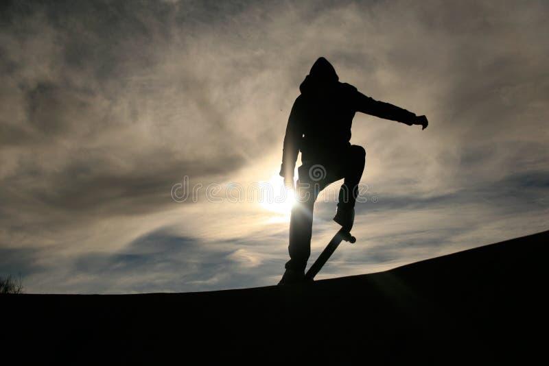 Planchiste faisant l'ollie dans le coucher du soleil images libres de droits