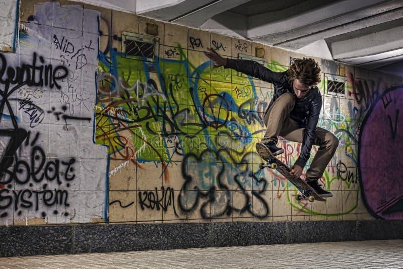Planchiste faisant un tour de planche à roulettes contre le mur de graffiti photo libre de droits